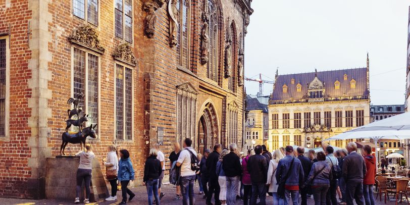 Besucherinnen und Besucher reihnen sich vor den Bremer Stadtmusikanten ein.