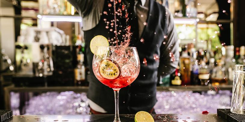 Ein Barkeeper gießt aus größerer Entfernung Flüssigkeit in ein Cocktailglas