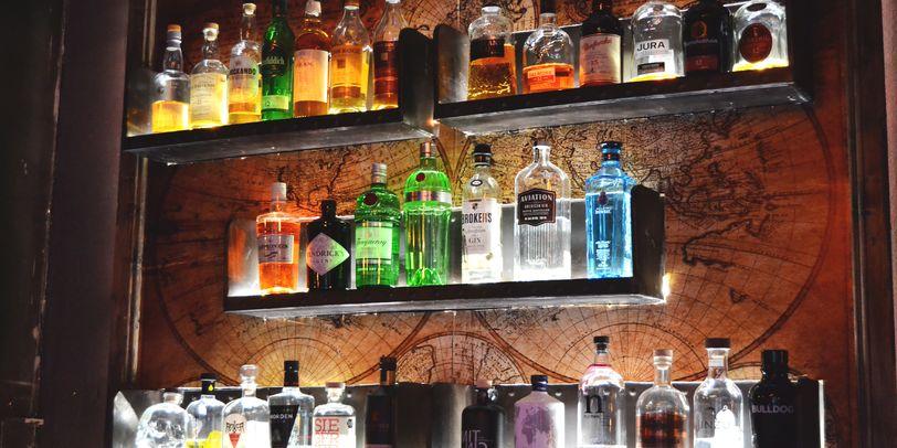 Verschiedene beleuchtete Alkoholsorten auf Regalen an der Wand