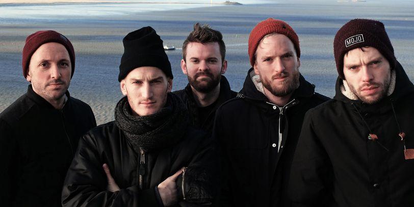 Eine Männergruppe steht steht vor einem Wattenmeer.