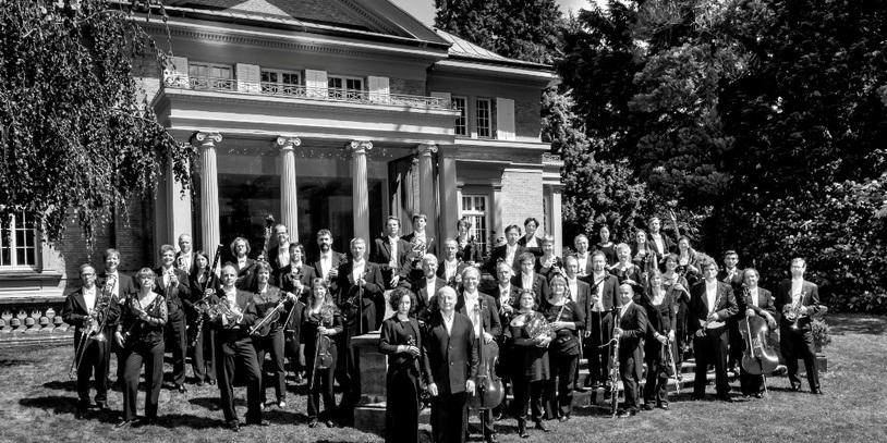 Schwarz-weiß Aufnahme der Orchester-Mitglieder vor einem herrschaftlichen Gebäude