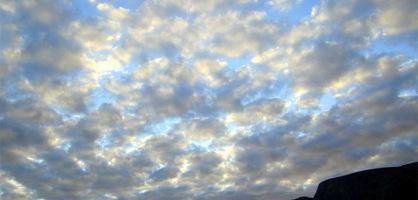 Himmel mit Wolken vor schroffem Felsen