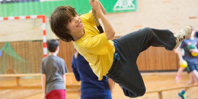 Ein Junge schwingt an einem Seil.
