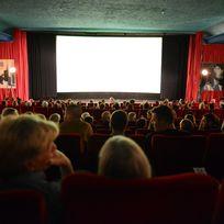 Viele Menschen sitzen in einem Kino. Vorne ist die Leinwand zu sehen. Links und rechts sind schwarze und rote Vorhänge.
