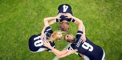 Drei Spielerinnen eines Damenteams besprechen sich in einem Kreis
