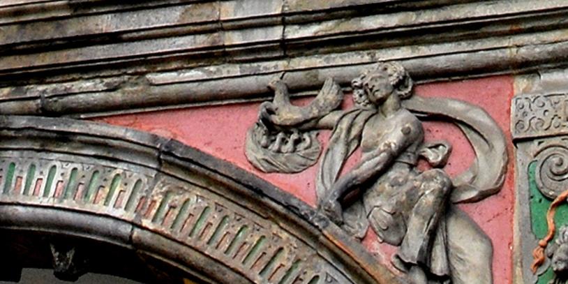 Gluckhenne mit ihren Küken über dem zweiten Arkadenbogen des Rathauses.