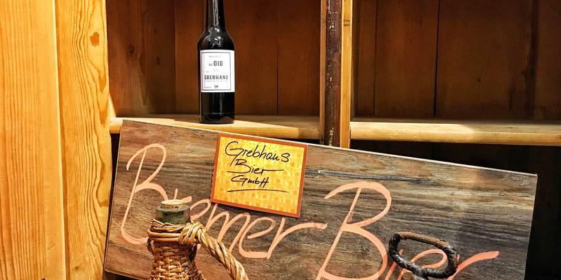 Ein Regal mit einer Flasche Grebhan's, davor ein Schild mit der Aufschrift Bremer Bier.