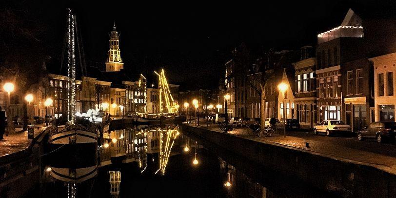 Groninger Kanäle bei Nacht mit beleuchteten Schiffen.