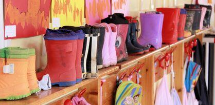 Bunte Gummistiefel und Turnbeutel stehen an einer Garderobe im Kindergarten