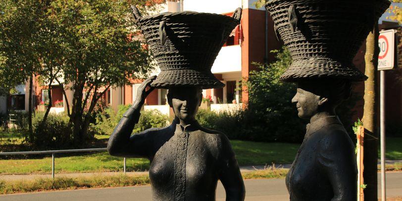 Blick auf zwei Bronze Figuren die Körbe auf dem Kopf tragen in Bremen Habenhausen