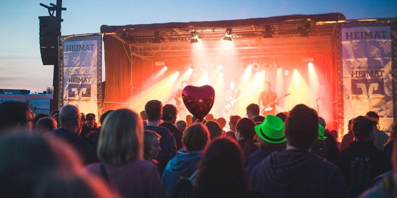 Viele Menschen schauen abends auf eine rote beleuchtete Bühne