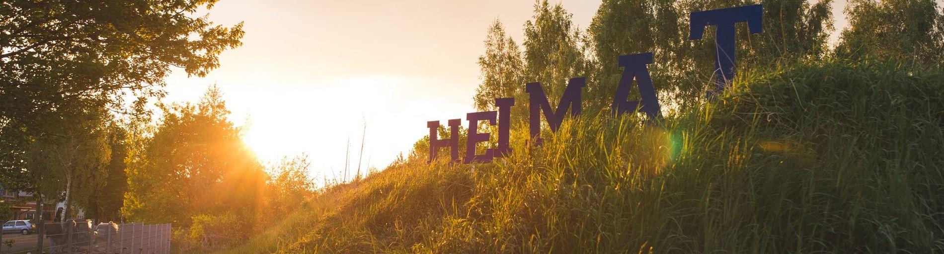 """Große Buchstaben stehen auf einer Wiese und bilden das Wort """"Heimat"""""""