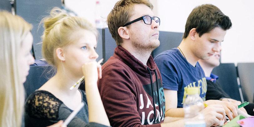 Studentinnen und Studenten sitzen in einer Vorlesung.