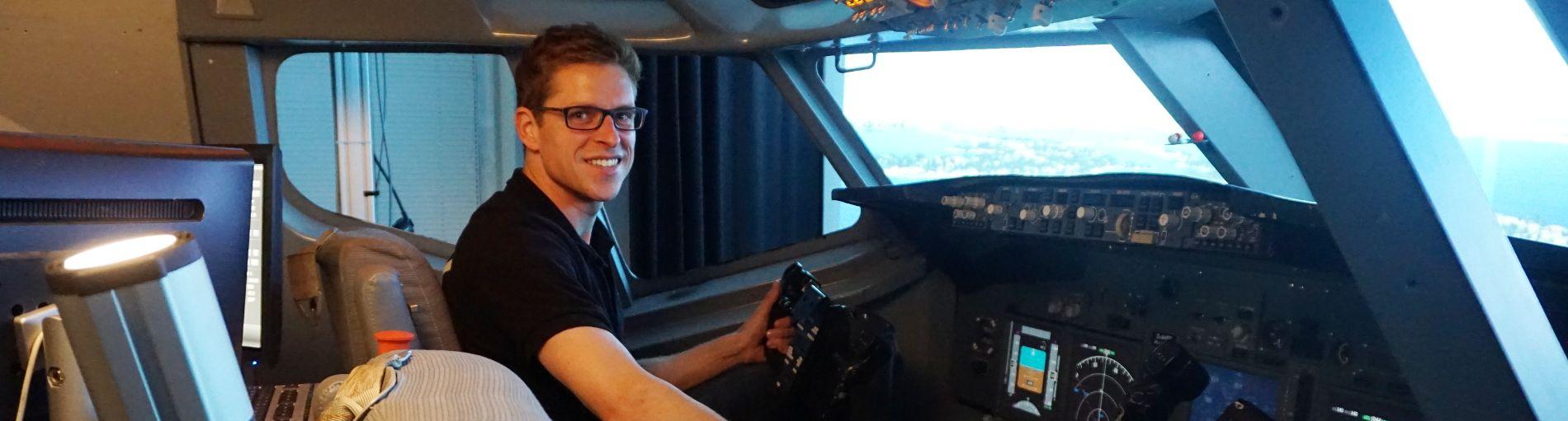 Christian Siegmund lächelt im Flugsimulator in die Kamera.