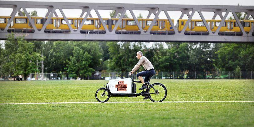 Ein Man fährt auf einem Lastenrad.