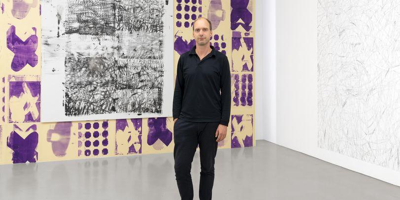 Der Kurator der Ausstellung steht vor einem bunten Gemälde.