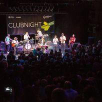 Ein Konzert während der jazzahead Clubnight. Eine Band steht hell erleuchtet auf der Bühne, vor dem vollen dunklen Publikum.