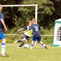 Drei Jungs spielen Fußball auf einem Rasenplatz