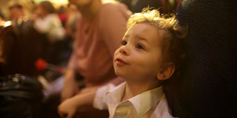 Ein kleiner Junge auf einem Sitz in einem Theatersaal