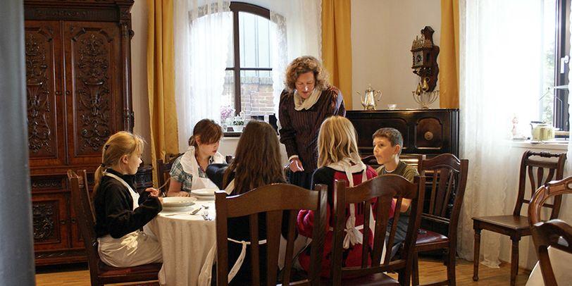 Auf dem Bild sieht man eine Kindergruppe, die in altertümlicher Kleidung gemeinsam kocht.