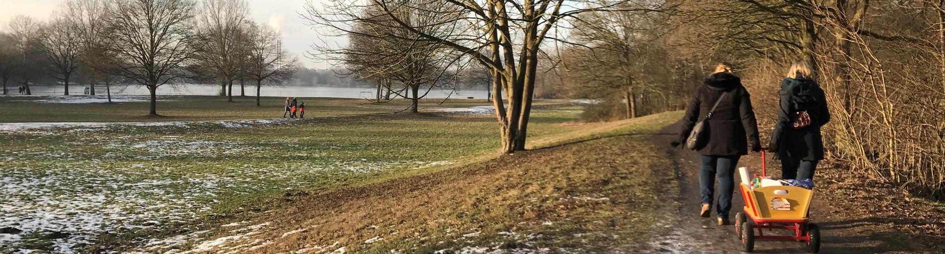 Zwei Frauen ziehen einen Bollerwagen durch eine winterliche Landschaft