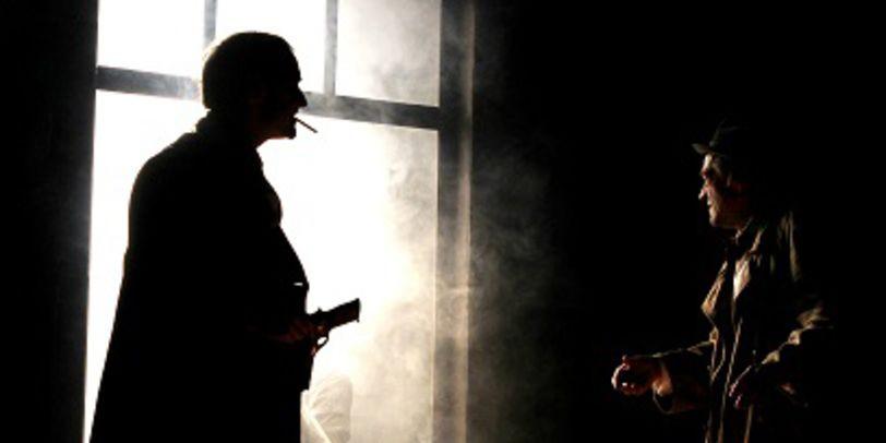 Silhouetten zweier Männer im Rauch vor einem Fenster