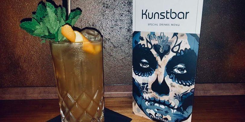 Ein Cocktail neben der Kunstbarkarte