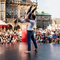 Eine Bühne steht mitten auf dem Bremer Marktplatz. Auf der Bühne sind ein Mann und eine Frau, die etwas vorführen. Um die Bühne herum stehen viele Zuschauer*innen.