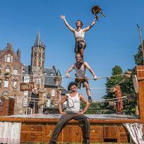 Artisten posieren vor einem altertümlichen Boxring. Im Hintergrund ist ein Schloss zu sehen.