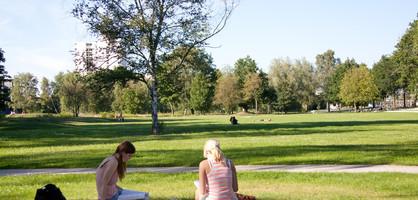 Grünanlage mit zwei Frauen, die im Gras sitzen und lesen