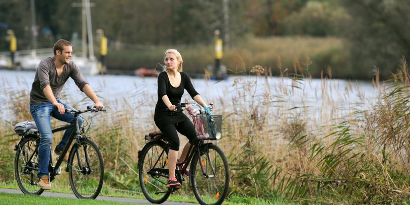 Ein Pärchen fährt an der Lesum Fahrrad