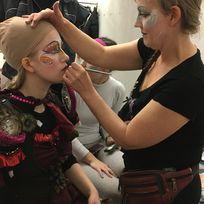 Eine Frau schminkt eine Kostümträgerin für den Karneval