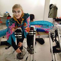 Eine Stelzenläuferin zieht die Stelzen für den Karneval an