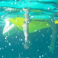 Kinderbeine unter Wasser mit Luftmatratze