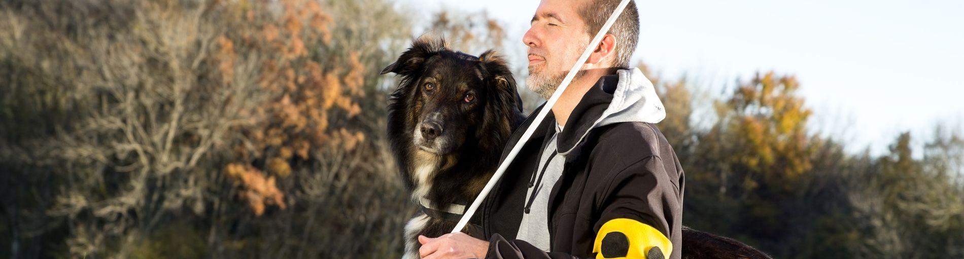 Ein Mann hockt auf einem Weg neben einem Blindenhund, in der Hand hält er einen Langstock. Der Mann hat die Augen geschlossen und genießt die Natur.