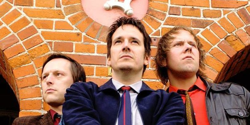3 Männer mit Krawatten und einer Trommel in der Hand. Im Hintergrund der Bremer Schlüssel.