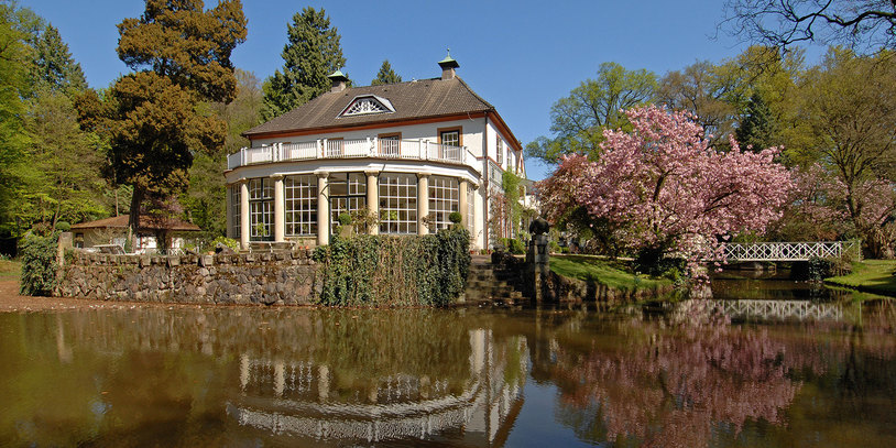 Ein herrschaftliches Gut in einem angelegten Garten mit See.