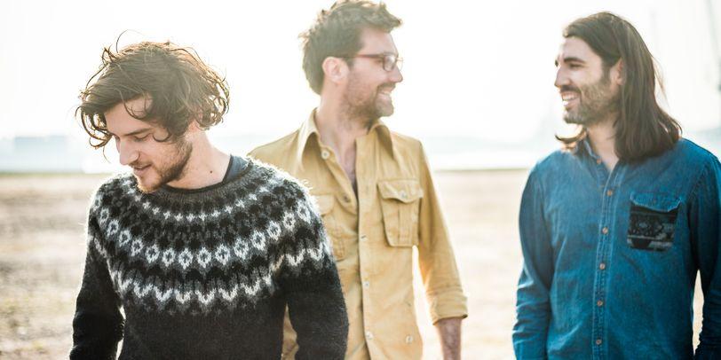 3 Männer stehen auf offenem Feld. Der Hintergrund ist sehr hell.