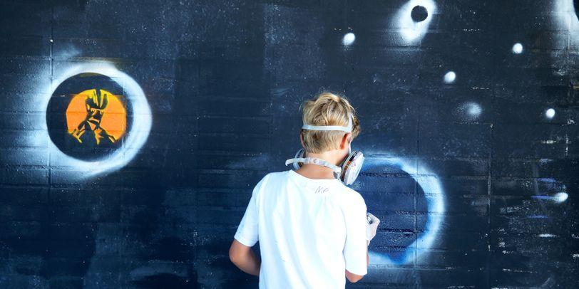 Ein Junge sprüht auf eine dunkle Wand ein Graffiti.