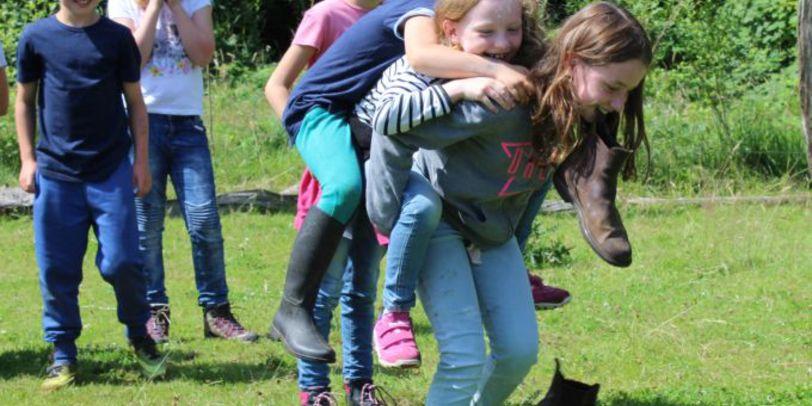 Kinder tragen einander Huckepack beim Spielen auf der Wiese.