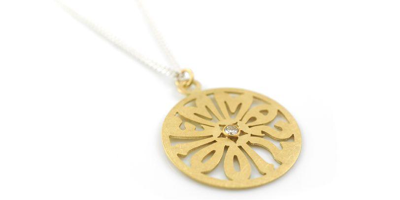 Eine Kreisförmige Namenskette in Gold mit einem Brillanten in der Mitte.