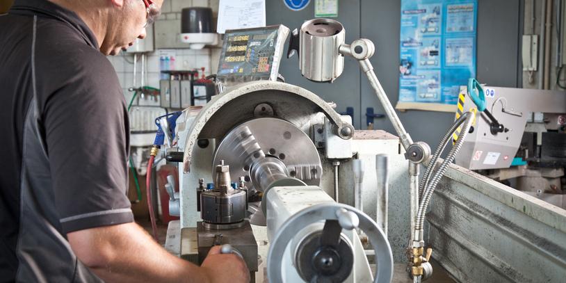 Ein Mann mit Schutzbrille arbeitet an einer Maschine.