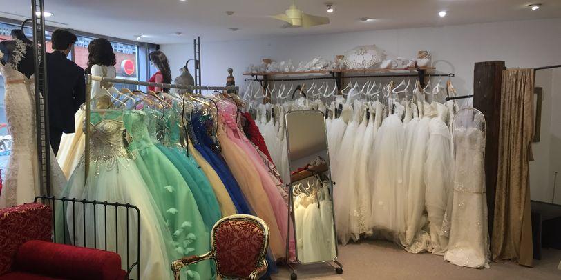 Blick in einen Laden mit weißen und bunten Hochzeitskleidern