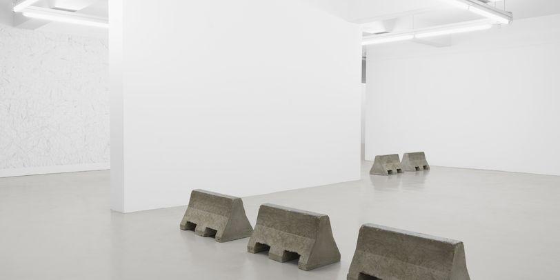 Schwere Betonpfeiler stehen in einem weißen Raum.