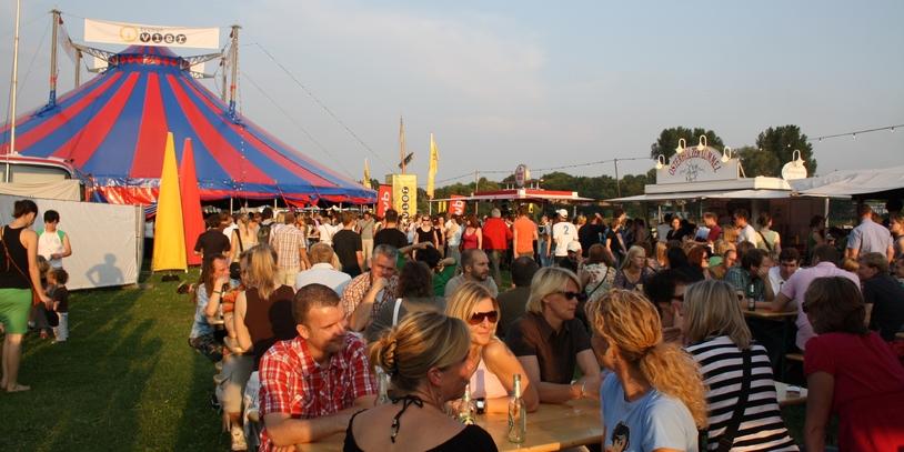 Menschen an Tischen vor Zelt