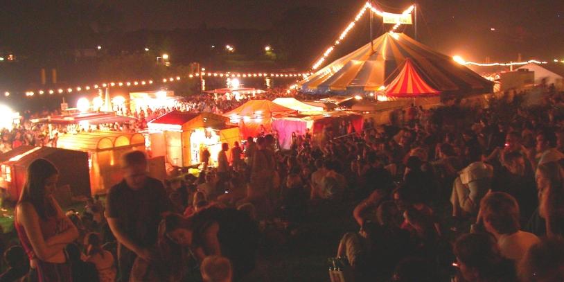 Menschen am Deich vor beleuchteten Zelte