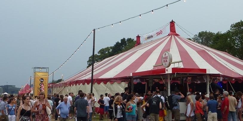Menschen an Bierbude vor Zelt