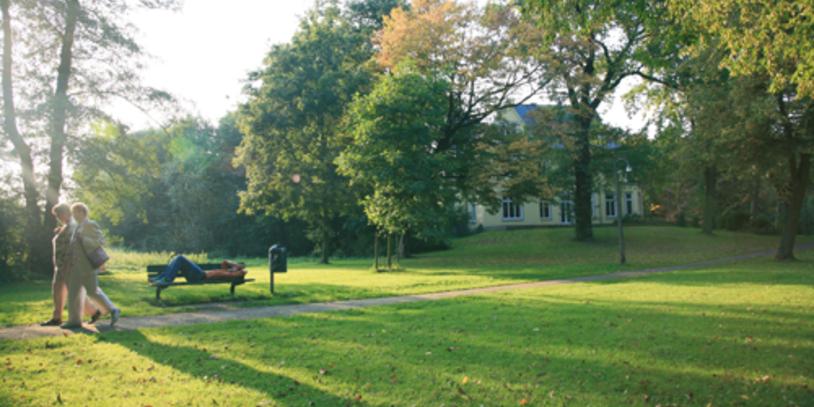 Spaziergänger und ein Mann auf einer Bank im Oslebshauser Park.
