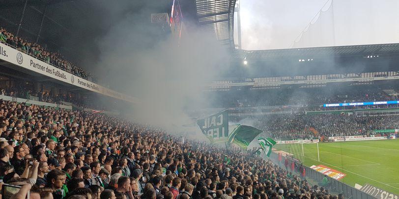 Zu sehen sind Fans in der Ostkurve im Weserstadion. Die Fans feuern Werder Bremen an.