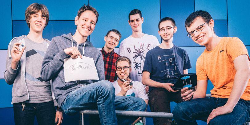 Team plan@earth posieren auf einem Geländer für die Kamera